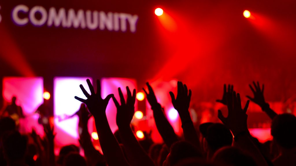 Hands raised in air with red background. The word community is blurred in background.