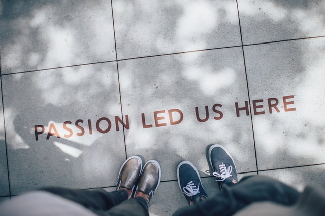 "two person standing on gray tile paving with text saying ""passion led us here"" on ground"