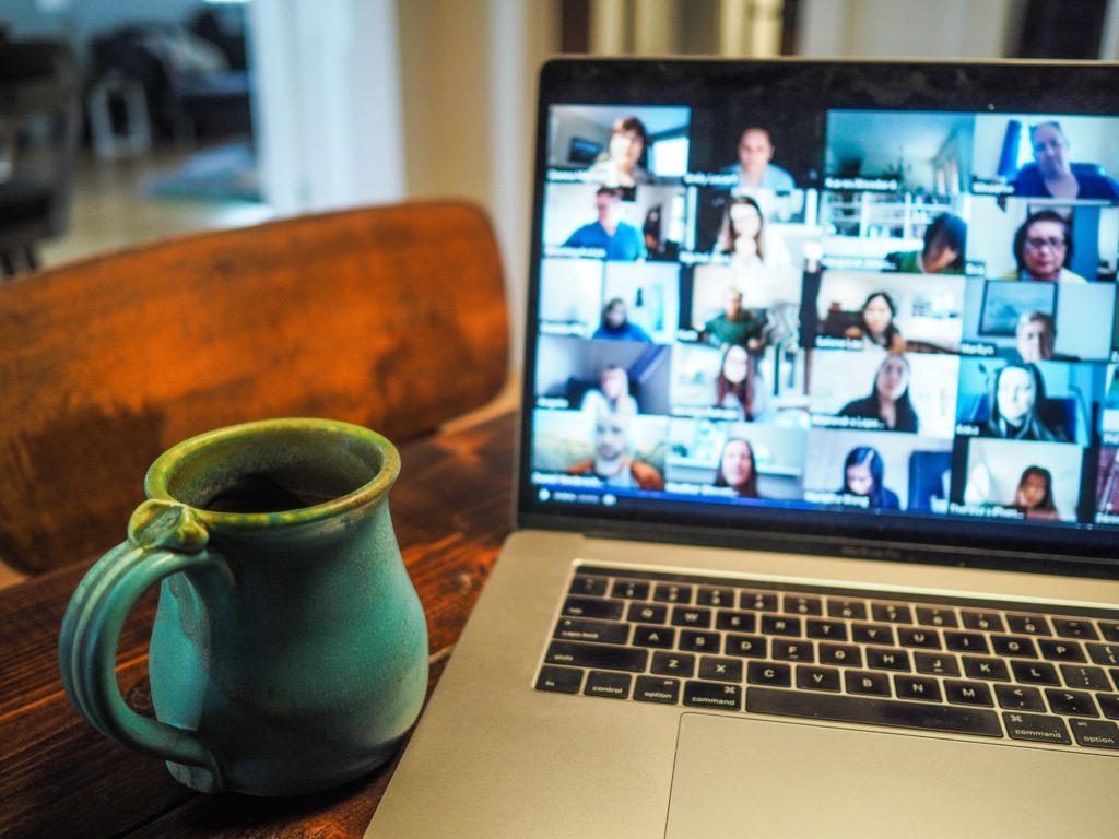 coffee cup and laptop displaying online meeting
